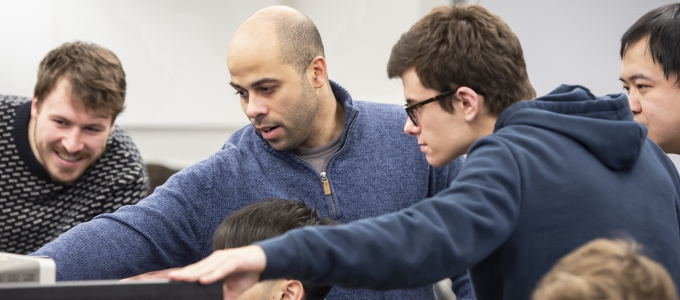Professor showing students something on a computer screen