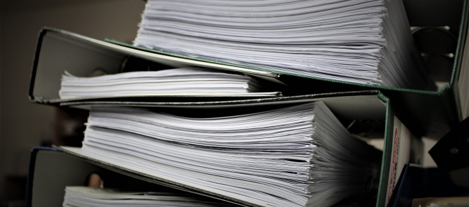 a stack of binders full of papers